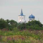 Свято-Преображенский храм в Коньково виднеется из-за макушек деревьев при подъезде к селу