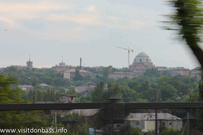Огромный купол даже в недостроенном виде затмевает шпили домов-символов Мариуполя (слева)