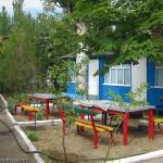 Обеденные столы около домиков на базе отдыха Монтажник, первый спуск Мелекино