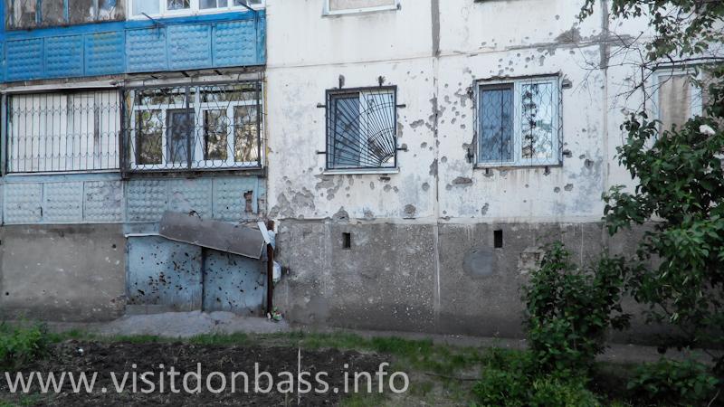 Следы от осколков на стене дома после обстрела микрорайона Восточный в Мариуполе